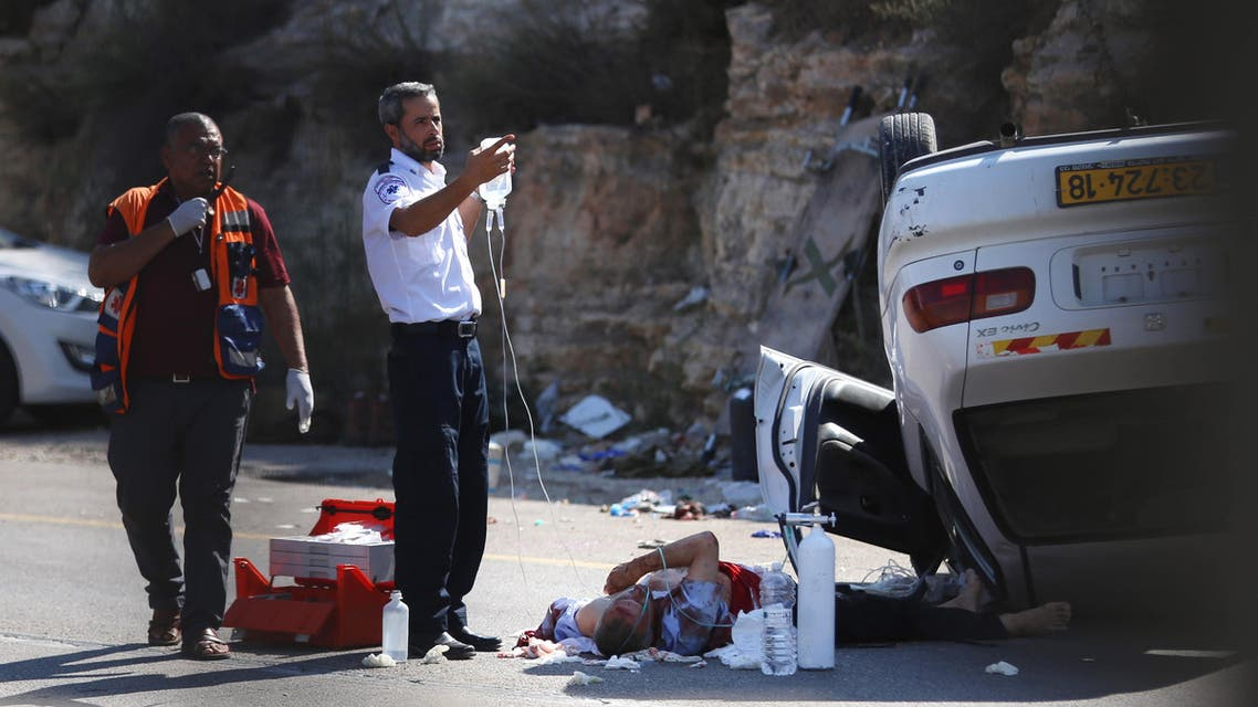 """AM6628 - RAMALLAH, WEST BANK, - : Israeli medics treat a soldier wounded in a run-over car attack at a junction midway between Ramallah and Nablus in the Israeli-occupied Palestinian territory on August 6, 2015. A driver rammed a car into a group of Israeli soldiers in the West Bank, wounding three of them, before troops halted the vehicle with gunfire. Two of the three wounded soldiers """"sustained severe injuries,"""" according to the Israeli military, while media said the driver was taken to a Jerusalem hospital. AFP PHOTO / STR"""
