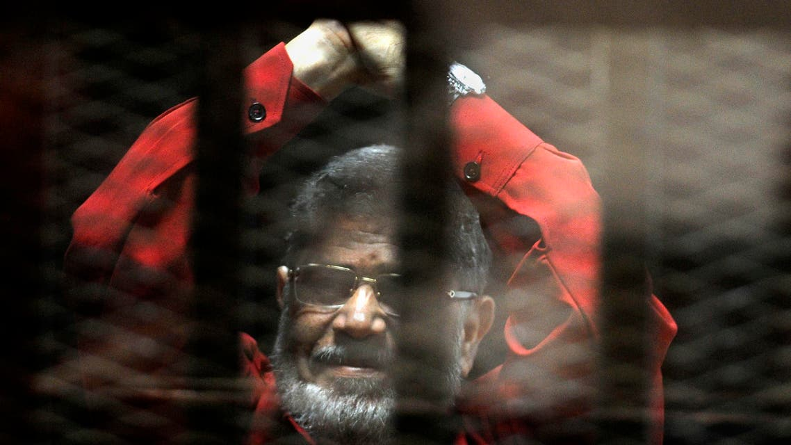 Ousted Egyptian President Mohammed Morsi, wearing a red jumpsuit that designates he has been sentenced to death, raises his hands inside a defendants cage in a makeshift courtroom at the national police academy, in an eastern suburb of Cairo, Egypt, Sunday, June 21, 2015