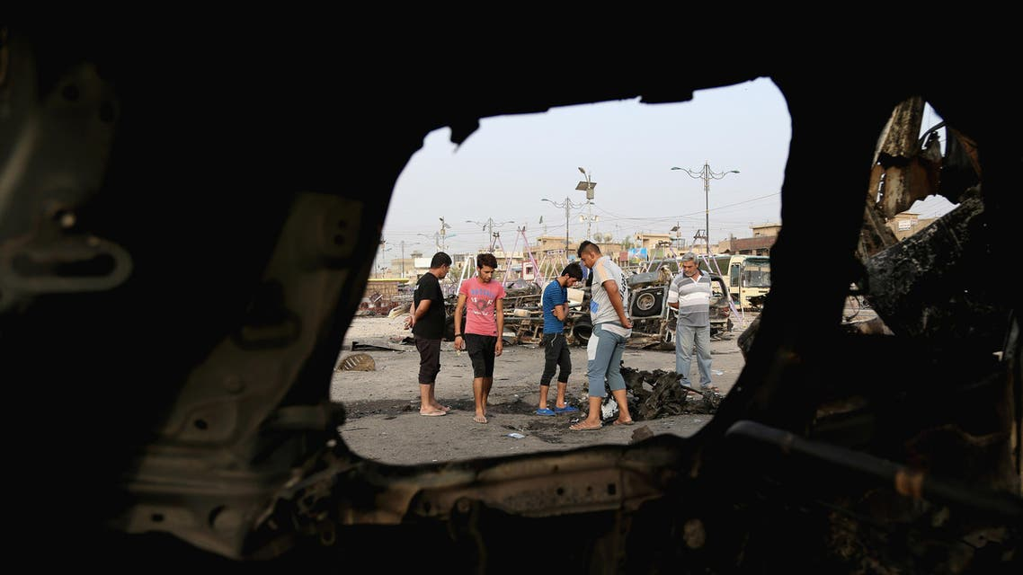 Civilians, seen through wreckage, inspect the aftermath of a car bomb explosion in the Shiite predominant district of Sadr city, Baghdad, Iraq, Thursday, Aug. 6, 2015. AP