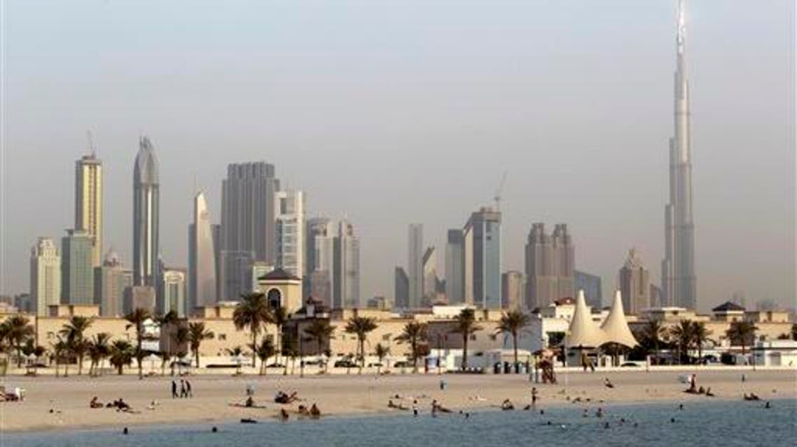 In this photo dated Thursday, July 26, 2012, people enjoy swimming at Jumeirah open beach with the city skyline in background, Dubai, United Arab Emirates. Not all Dubai beaches are hidden behind high-end hotels and waterfront palaces. Jumeirah Open Beach is one of the city's most popular, drawing everyone from Russian tourists and Arab families to Indian and Pakistani migrant workers relaxing on their day off. One you've had your fill of the white sand beach and sparkling Gulf waters, turn around to take in the view of Dubai's futuristic skyline. Facilities include showers and a rare cycle path. The nearby Jumeirah Beach Park offers more greenery and less ogling, but the upgrade comes with a 5 dirham ($1.36) entry fee. (AP Photo/Kamran Jebreili)