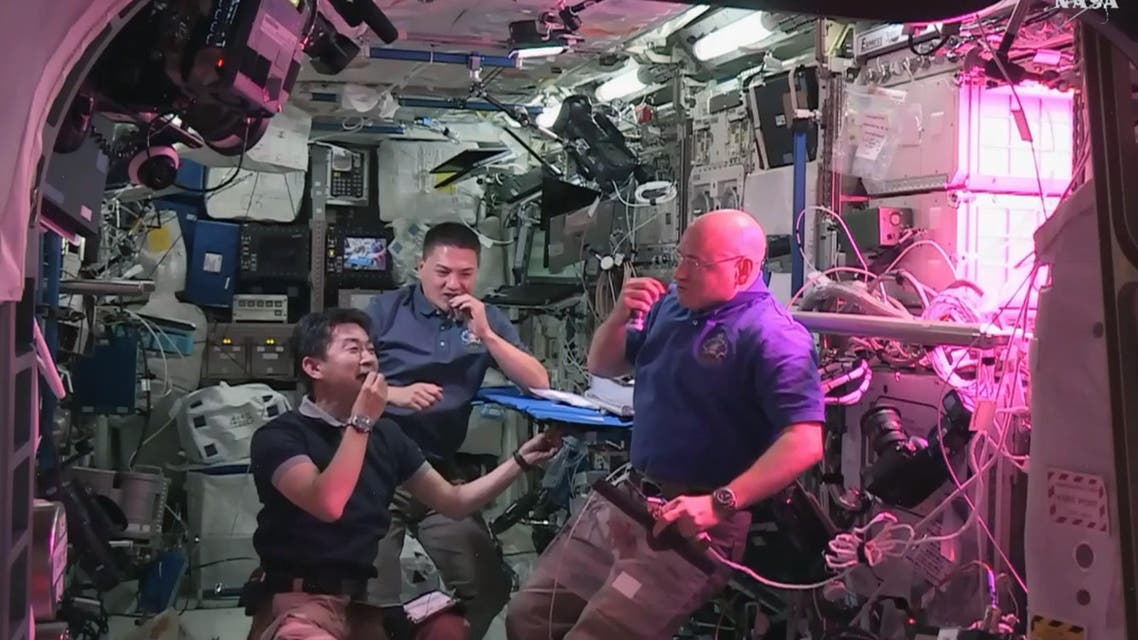 """This August 10, 2015 image from NASA TV shows L-R: Japan Aerospace Exploration Agency (JAXA) astronaut Kimiya Yui, with NASA astronauts Kjell Lindgren and Scott Kelly as they eat red romaine lettuce grown on board the International Space Station. Astronauts living at the International Space Station are about to take their first bites of space-grown lettuce, in what scientists described as another step toward enabling human missions to Mars. The red romaine lettuce was grown in a special plant-growing box called Veg-01, and was flown to space aboard the SpaceX Dragon cargo ship. The seeds are contained in rooting pillows, and were """"activated"""" by Kelly on July 8, NASA said. The plants grew for 33 days before being harvested. AFP PHOTO / HANDOUT / NASA TV"""