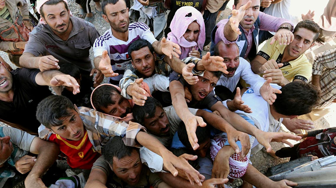 Displaced Iraqis from the Yazidi community gather for humanitarian aid at the Syria-Iraq border at Feeshkhabour border point, northern Iraq. (AP)