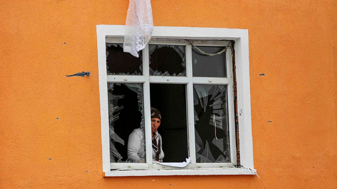 A woman looks on from her shattered window, damaged after an attack on a nearby police station in Istanbul