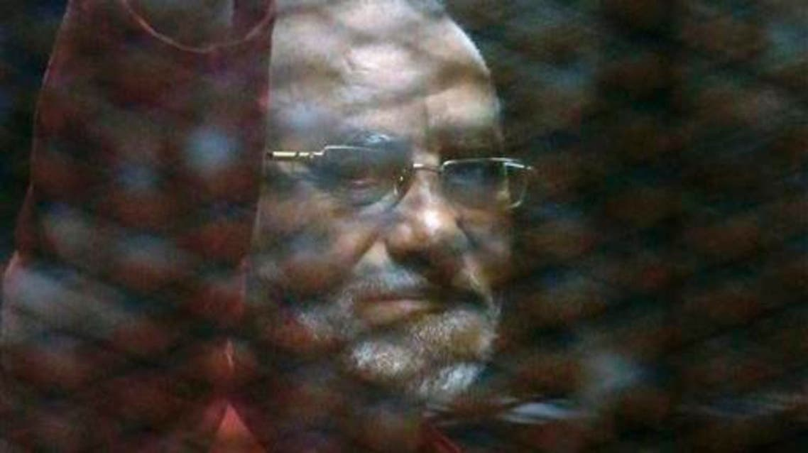 Muslim Brotherhood spiritual leader, Mohammed Badie wearing a red jumpsuit that designates he has been sentenced to death, waves from a defendants cage in a makeshift courtroom at the Torah prison, southern Cairo, Egypt, Tuesday, July 21, 2015. (AP Photo/Amr Nabil)