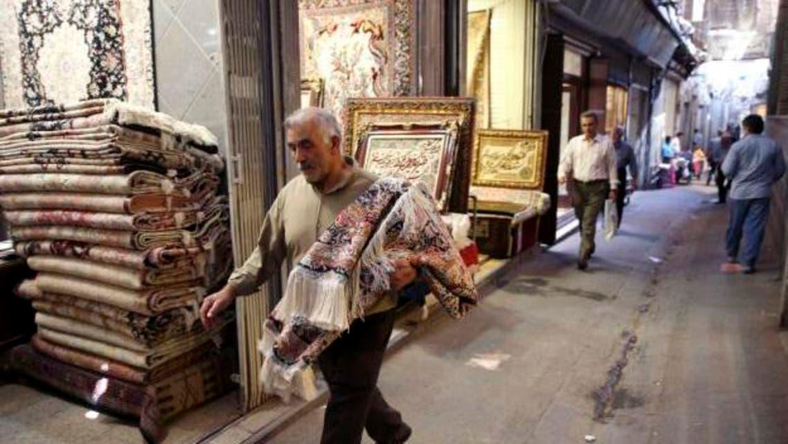 An Iranian man carries a carpet through Tehran's old, main bazaar, Iran. (AP)