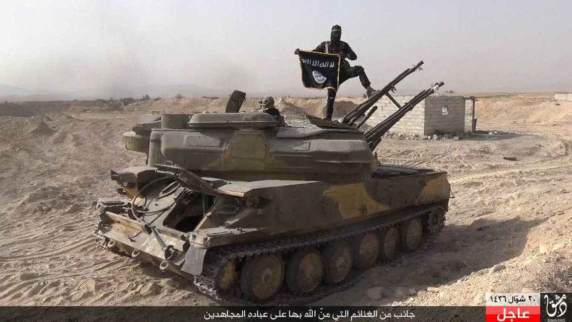 an Islamic State militant holds the group's flag as he stands on a tank they captured from Syrian government forces, in the town of Qaryatain southwest of Palmyra, central Syria. AP