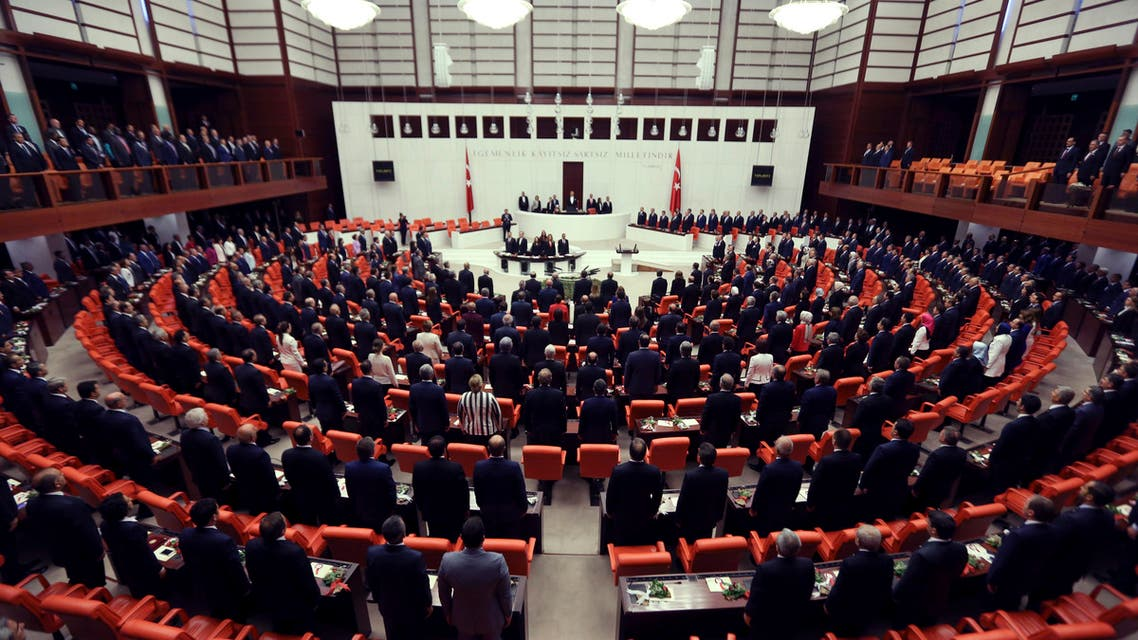 Newly elected legislators stand for national anthem before they take oaths during the Turkish parliament's first session in Ankara, Turkey, on Tuesday, June 23, 2015