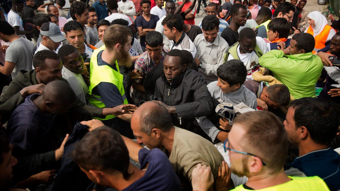 "Migrants scuffle for clothes distributed by a local NGO at a camp set near Calais, northern France, Sunday, Aug. 9, 2015. An estimated 2,500 migrants are currently at the windswept camp surrounded by sand dunes that sprung up when a state-approved day center for migrants was opened nearby. The ramshackle encampment of tents and lean-tos is referred to as the ""jungle,"" like the camps it replaced. (AP Photo/Emilio Morenatti)"