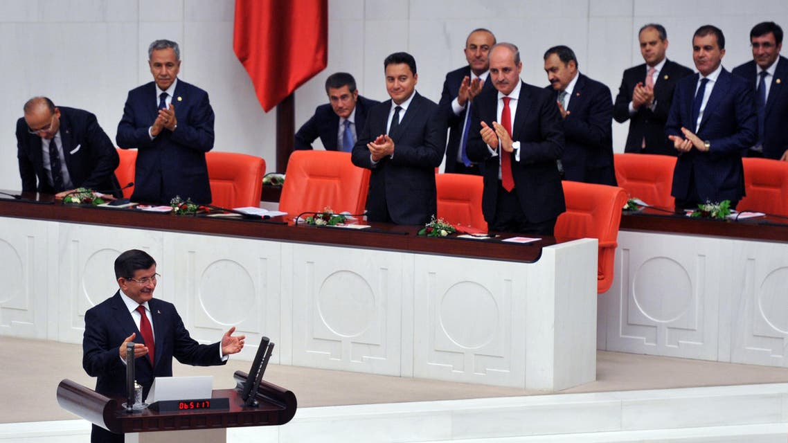 Turkey's Prime Minister Ahmet Davutoglu, left, reacts to cheering lawmakers before he takes his oath during the Turkish parliament's first session in Ankara, Turkey, on Tuesday, June 23, 2015. The ruling Islamic-rooted Justice and Development Party (AKP) came out first in the June 7 elections but lost its parliamentary majority. (AP Photo)