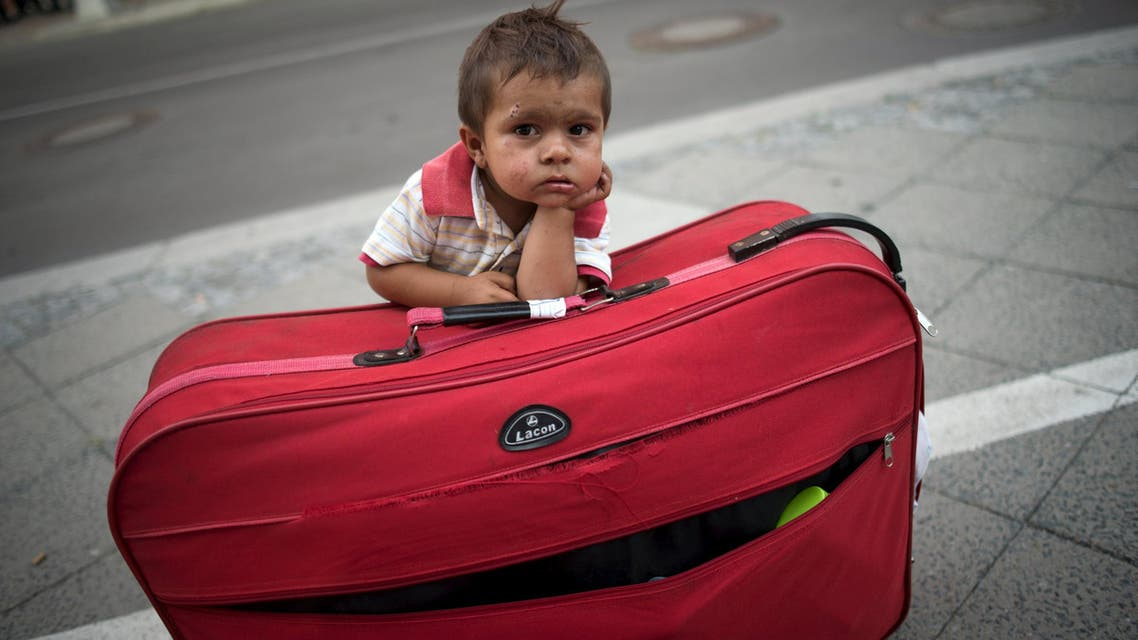 Migrant boy waits at his parents' suitcase as they leave the Berlin State Office for Health and Social Affairs with other newly arrived refugees who waited all day to apply for asylum in Berlin. (Reuters)