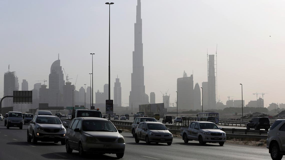 Cars pass by the city skyline with the Burj Khalifa, world tallest tower in background, Tuesday, July 28, 2015, in Dubai, United Arab Emirates. The United Arab Emirates has slashed gasoline subsidies, announcing Tuesday that it will raise the cost of a liter of regular gasoline by 24 percent amid globally low oil prices that have cut into the country's revenues. (AP Photo/Kamran Jebreili)