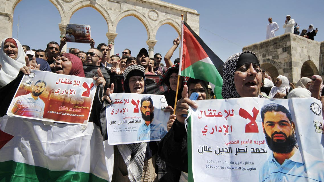 "Protestors hold up Palestinian flags and posters with pictures of Palestinian detainee Mohammed Allan and Arabic that reads ""no to the administrative detention, freedom for the lawyer prisoner, detained November 1, 2014,"" during a protest near the Dome of the Rock Mosque, in the Al Aqsa Mosque complex, in Jerusalem's old city, Friday, Aug. 14, 2015. Mohammed Allan who has been on a hunger strike for 60 days slipped into unconsciousness on Friday and was being treated in the intensive care unit at an Israeli hospital. (AP Photo/Mahmoud Illean)"
