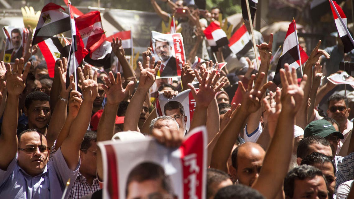 Members of the Muslim Brotherhood hold up pictures of their ousted President Mohammed Morsi during a protest two years after hundreds were killed in a single day when Egyptian troops moved in to disperse sit-ins by Islamist supporters of the Brotherhood, in the Talbia district of Giza, Egypt, Friday, Aug. 14, 2015.