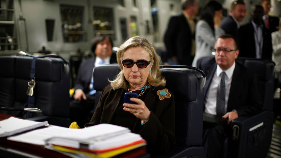 In this Oct. 18, 2011, file photo, then-Secretary of State Hillary Rodham Clinton checks her Blackberry from a desk inside a C-17 military plane upon her departure from Malta, in the Mediterranean Sea, bound for Tripoli, Libya. (AP)