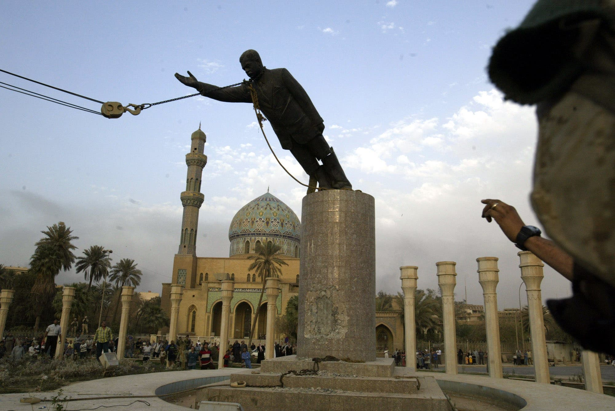 A U.S. marine watches a statue of Saddam Hussein being toppled in a square downtown Baghdad in 2003. (File photo: AP)