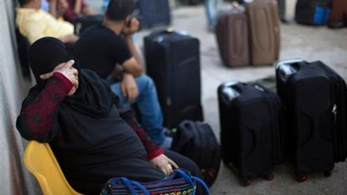 A Palestinian woman rests as she waits to cross the border into Egypt, at the Rafah crossing in the southern Gaza Strip, Monday, Aug 17, 2015. (AP)