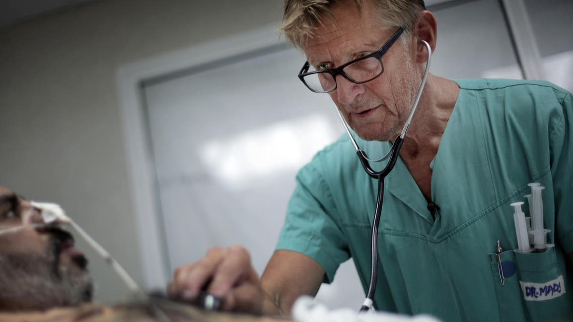 """Mads Gilbert, Norwegian doctor who has volunteered at Shifa on and off for 17 years, treats a man at the emergency room of the Shifa hospital in Gaza City. Working at Shifa requires ingenuity. The power goes off repeatedly as aging hospital generators buckle under daily rolling blackouts Gaza residents have lived with for years. """"If we are in the middle of an operation (and) lights go out, what do the Palestinians do? They pick up their phones, and they use the light from the screen to illuminate the operation field,"""" said Gilbert. (AP Photo/Khalil Hamra)"""