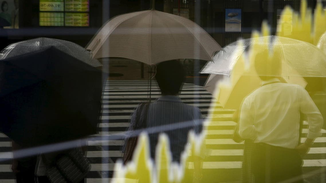Pedestrians holding an umbrella are reflected on an electronic board showing the graph of the recent fluctuations of Japan's Nikkei average outside a brokerage in Tokyo, Japan, August 17, 2015. Japanese stocks rose on Monday morning on relief the contraction in the world's third-largest economy was not as bad as the market had expected. REUTERS/Yuya Shino