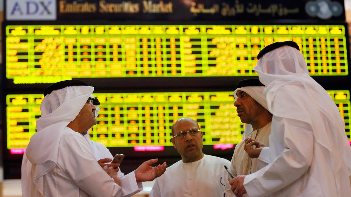 Investors speak in front of a screen displaying stock information at the Abu Dhabi Securities Exchange June 25, 2014. (Reuters)