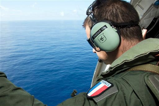 In this photo released on Sunday, Aug. 9, 2015 by the French Army Communications Audiovisual office (ECPAD) a crew member looks out aboard a CASA 235 plane from the 181st Air Detachment of the French Air Force taking part in the search for wreckage from the missing MH370 plane off the coasts of the French island of La Reunion. A French search plane lifted off Friday for a bird's-eye view of Reunion Island, seeking any more potential debris from Malaysia Airlines Flight 370. French authorities said Friday they've launched a one-week-long operation with boats and aircraft scouring the Indian Ocean island, where a wing fragment was discovered nine days ago. (Patrick Becot/ ECPAD via AP)