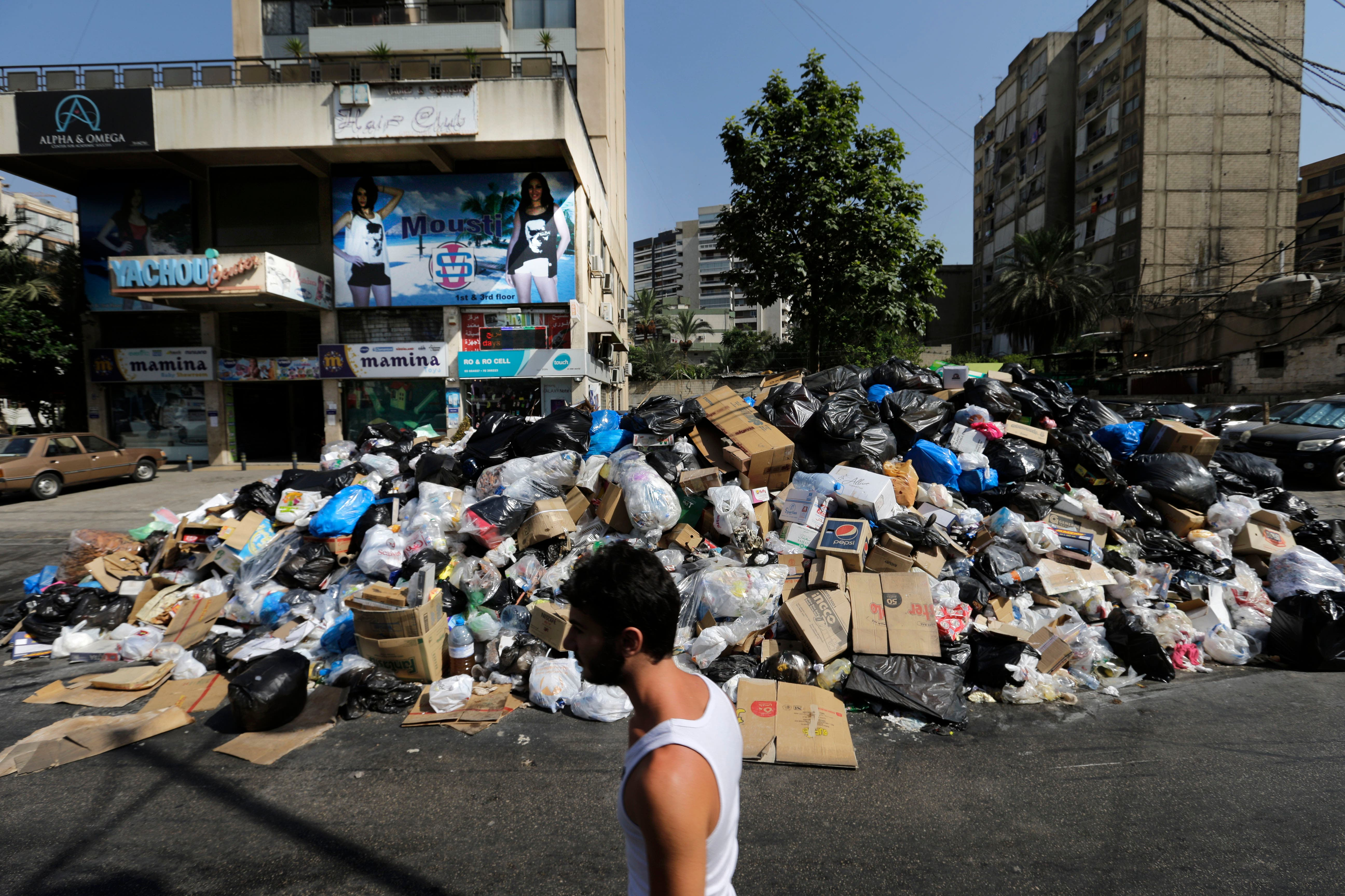 A Lebanese man passes a pile of garbage blocking a street in east Beirut, Lebanon, Monday, Aug. 17, 2015. AP