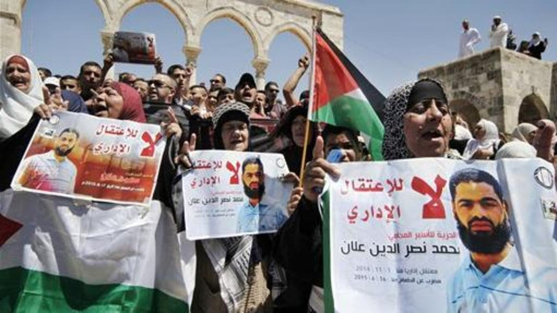 """In this Friday, Aug. 14, 2015 file photo, protestors hold up Palestinian flags and posters with pictures of Palestinian detainee and hunger striker Mohammed Allan during a protest in the Al Aqsa Mosque complex, in Jerusalem's Old City. Allan spent his college years as an activist, fighting for Palestinian rights as a member of the student wing of the Palestinian Islamic Jihad militant group. Now, verging on death and shackled to a hospital bed, the man accused by Israel of affiliation with terrorists has put a spotlight on Israel's controversial detention and force-feeding policies. Arabic reads """"no to administrative detention"""" and calls for freedom for Allan. (AP Photo/Mahmoud Illean, File)"""