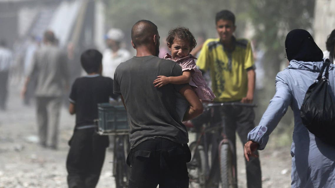 Man carries a girl reacting at a site hit by what activists said were air strikes by forces loyal to Syria's President Bashar al-Assad on a marketplace in the Douma neighborhood of Damascus, Syria Reuters