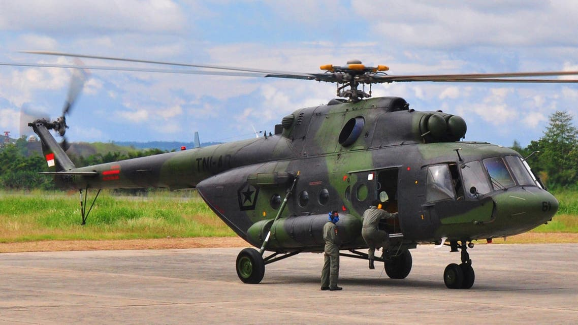 Indonesian air force personnel prepare a military helicopter at Sentani airport in Jayapura on August 18, 2015 in preparation for the search operation