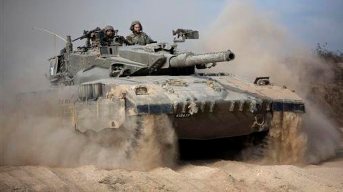 In this Friday, July 18, 2014 file photo, an Israeli tank moves into position near Israel and Gaza border. A fierce debate is raging within Israel's military over the extent to which soldiers should be held legally accountable for their actions during last year's Gaza war, with commanders increasingly at odds with military lawyers.(AP Photo/Dusan Vranic, File)