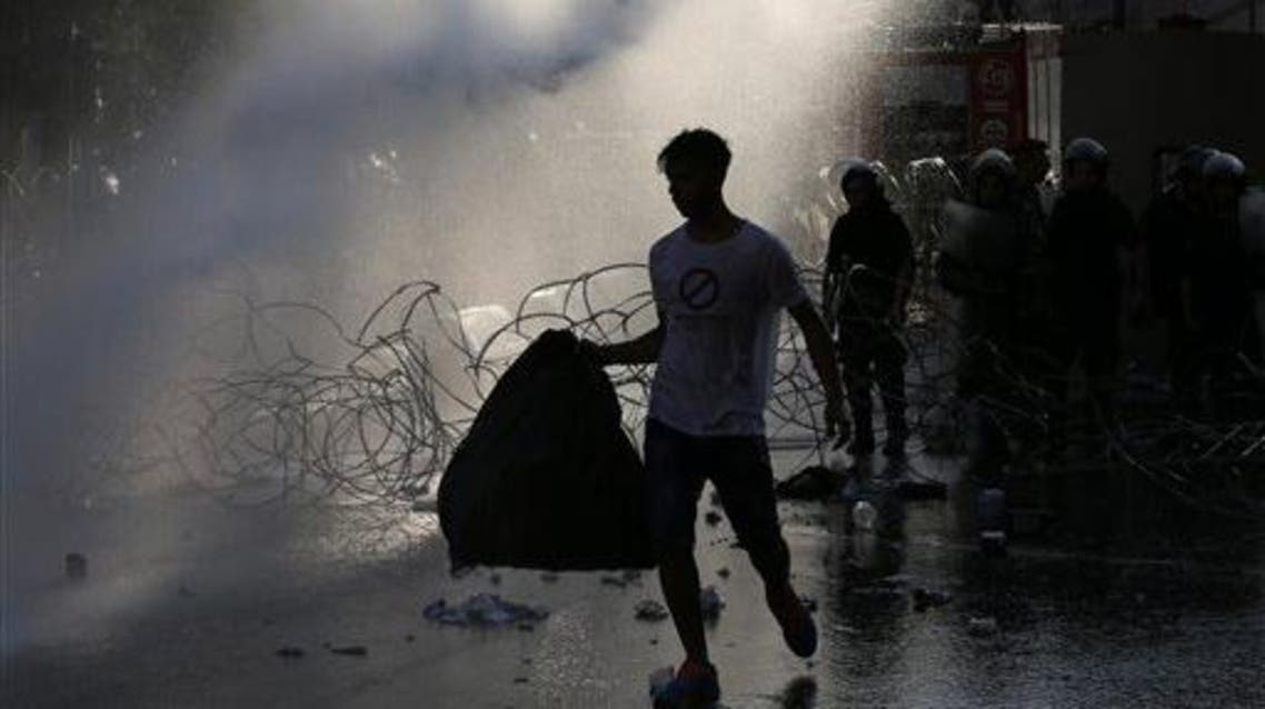 A Lebanese activist carries a plastic bag of garbage as he sprayed by water cannons, during a protest against the ongoing trash crisis (AP)