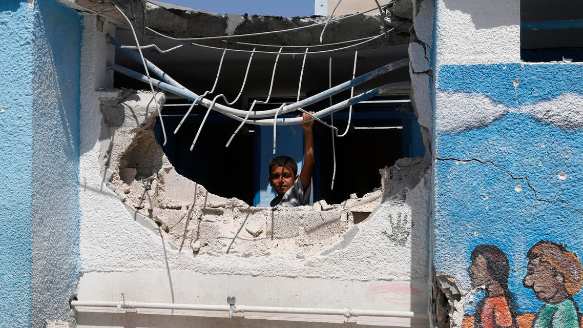 A boy looks through the wall of a building damaged by an Israeli strike at the Abu Hussein U.N. school in the Jebaliya refugee camp in the northern Gaza Strip on Wednesday, July 30, 2014. Israeli tank shells slammed into a crowded U.N. school Wednesday sheltering Gazans displaced by fighting, killing more than a dozen and wounding tens after tearing through the walls of two classrooms, a spokesman for a U.N. aid agency and a health official said. The Israeli military said mortar shells had been fired from near the school, and that soldiers fired back. (AP Photo/Hatem Moussa)