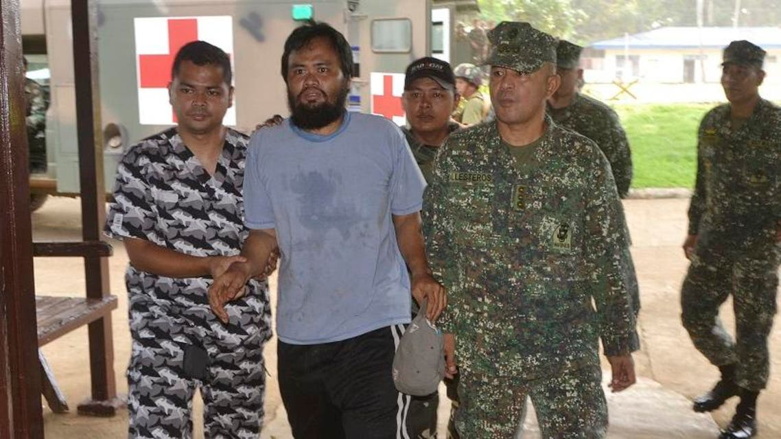 Escaped hostage Philippine coast guard Seaman First Class (SN1) Rod Pagaling, center, is escorted inside a military camp in Jolo, Sulu province, southern Philippines Thursday, Aug. 20, 2015.