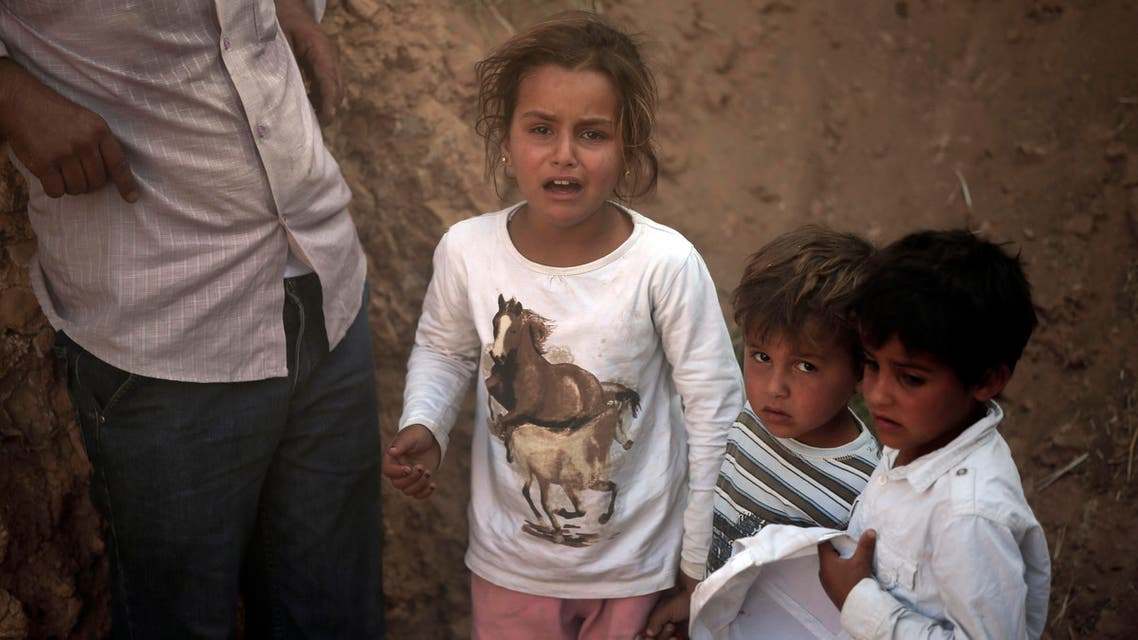 Syrian refugee children are stuck after breaking the border fence and crossing into Turkey from Syria, in Akcakale, Sanliurfa province, southeastern Turkey, Sunday, June 14, 2015. AP