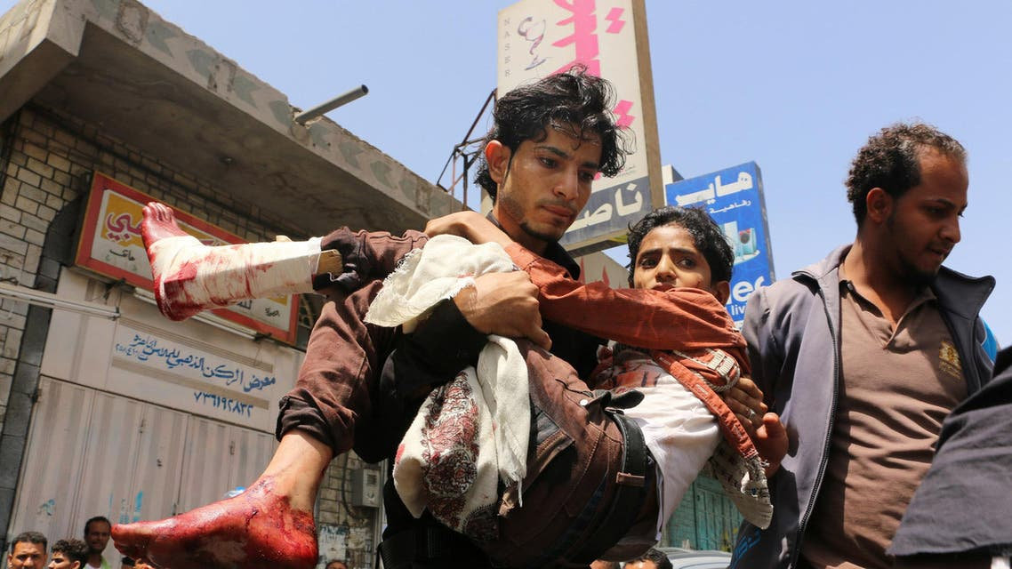 In this April 26, 2015, file photo, a man carries a boy who was injured during a crossfire between tribal fighters and Shiite militia known as Houthis, in Taiz, Yemen. In a report released Tuesday, Aug. 18, 2015l AP
