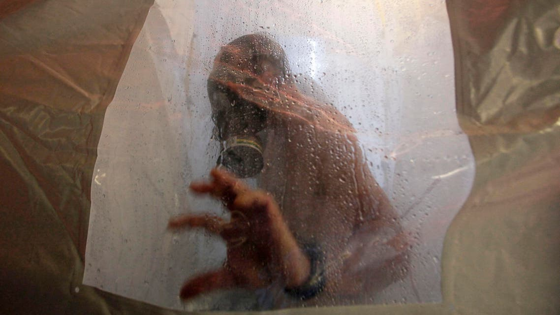 A crew member of the Danish warship Esbern Snare enters a decontamination shower wearing a gas mask during drills at sea between Cyprus and Syria, Sunday, Jan. 5, 2014.  (AP)