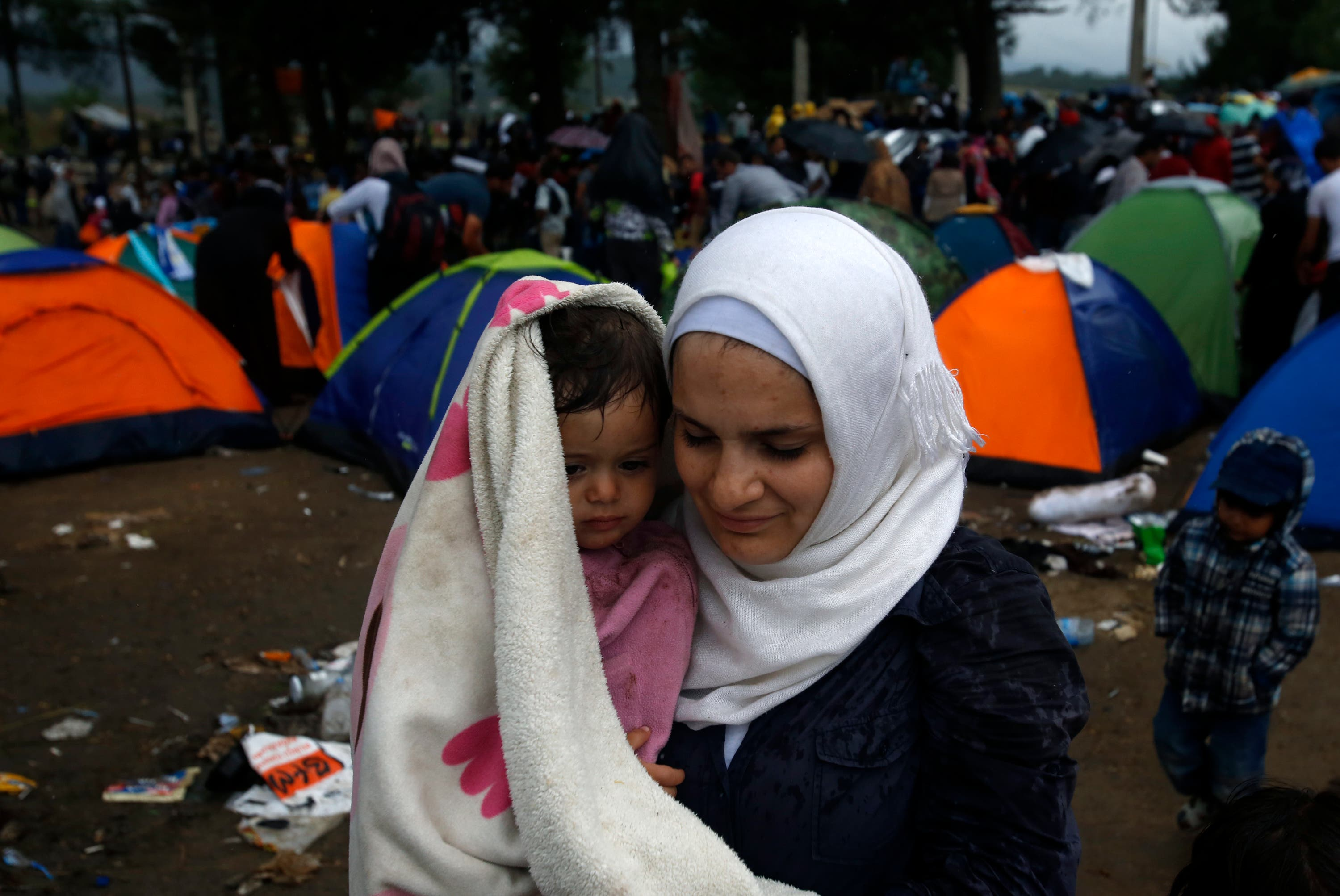 A migrant woman holds a child on the border line with Greece, near the train station of Idomeni, northern Greece, Saturday, Aug. 22, 2015. (AP)