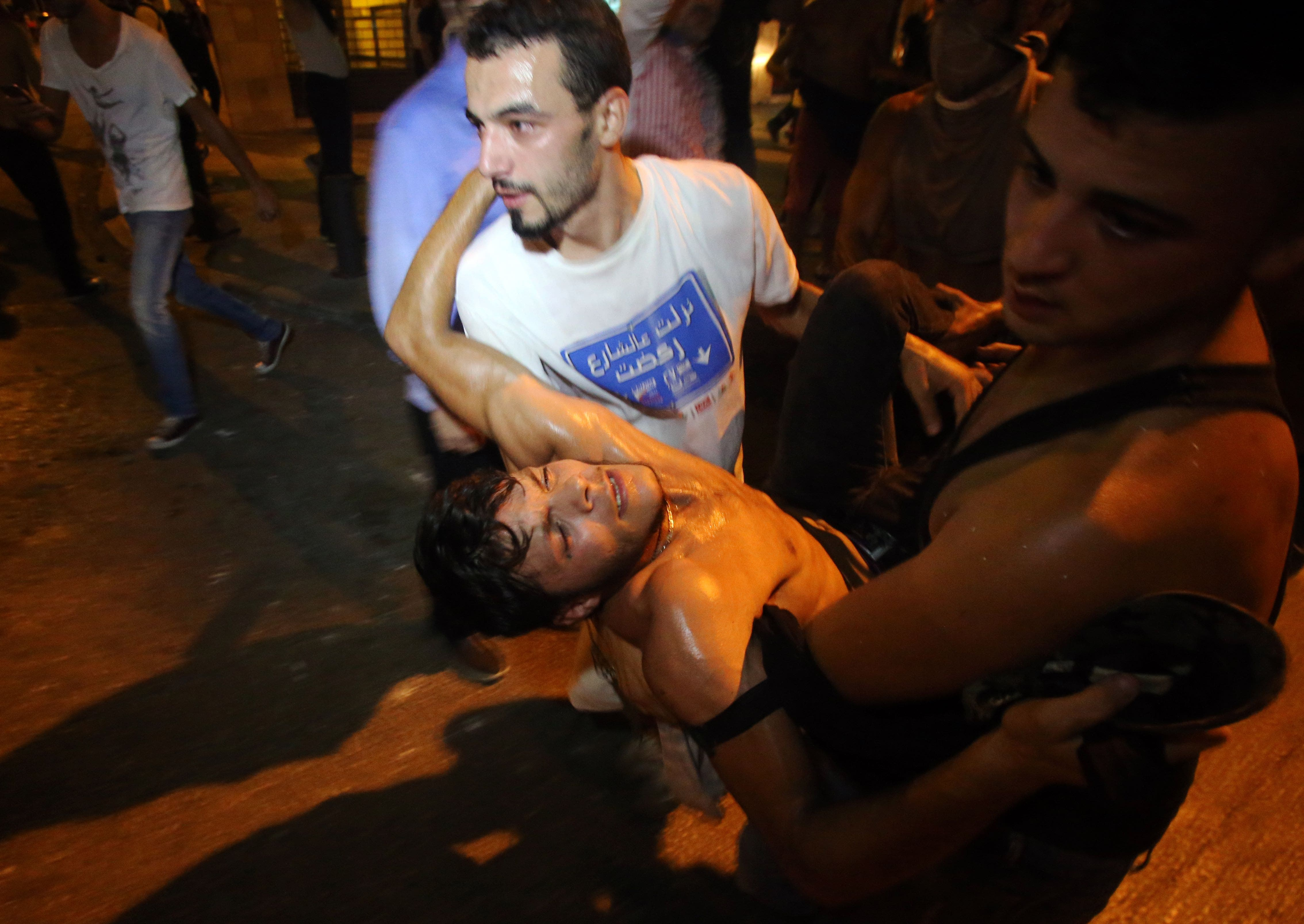 Lebanese demonstraters carry a man injured in clashes with security forces (AFP)
