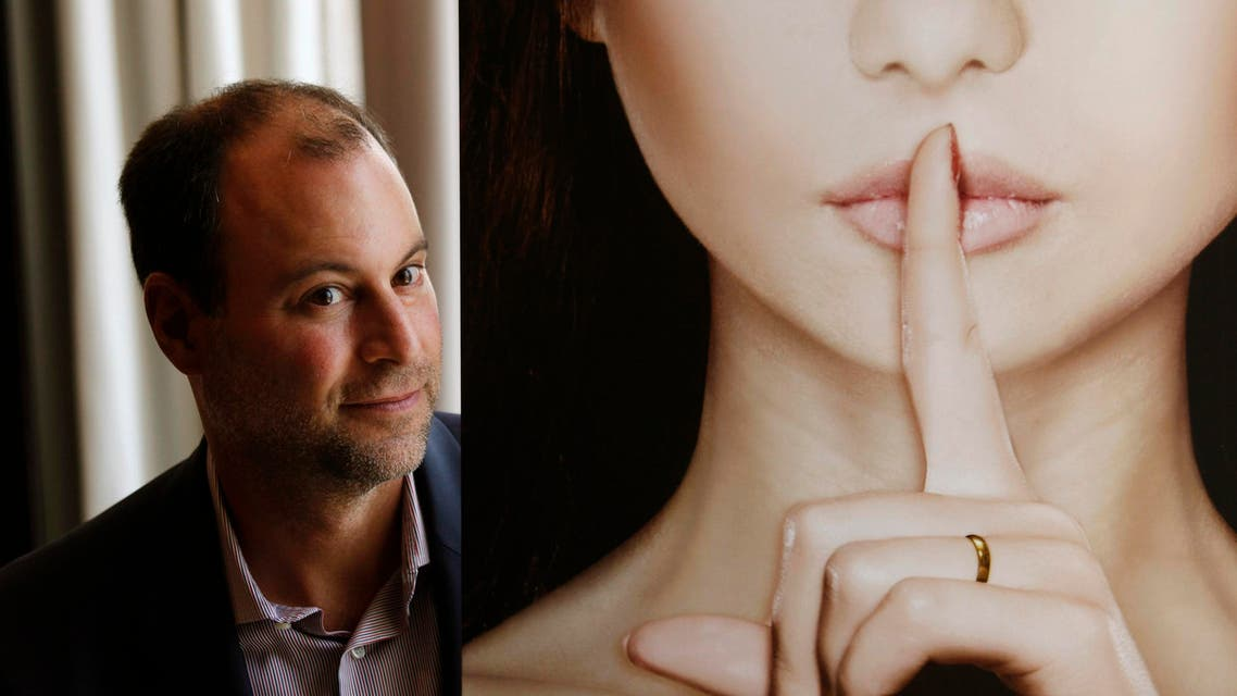 Ashley Madison founder Noel Biderman poses with a poster during an interview at a hotel in Hong Kong in this August 28, 2013. (Reuters)