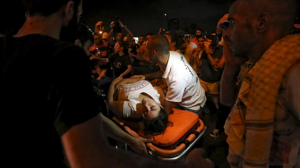 A wounded woman is moved on a stretcher by medics during a protest against corruption and rubbish collection problems near the government palace in Beirut, August 22, 2015. (Reuters)