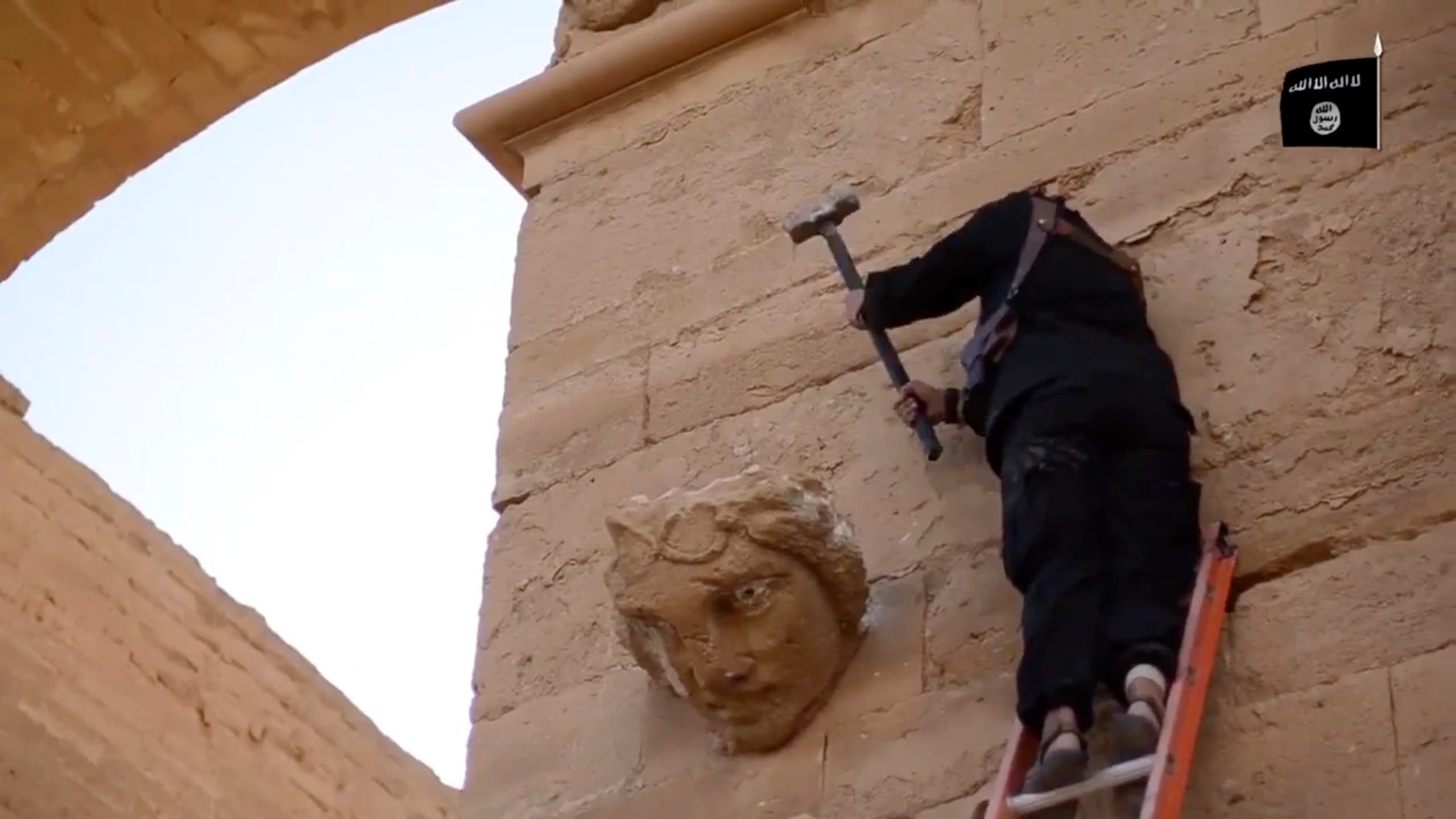 a militant hammers away at a face on a wall in Hatra, a large fortified city recognized as a UNESCO World Heritage site. (File photo: AP)