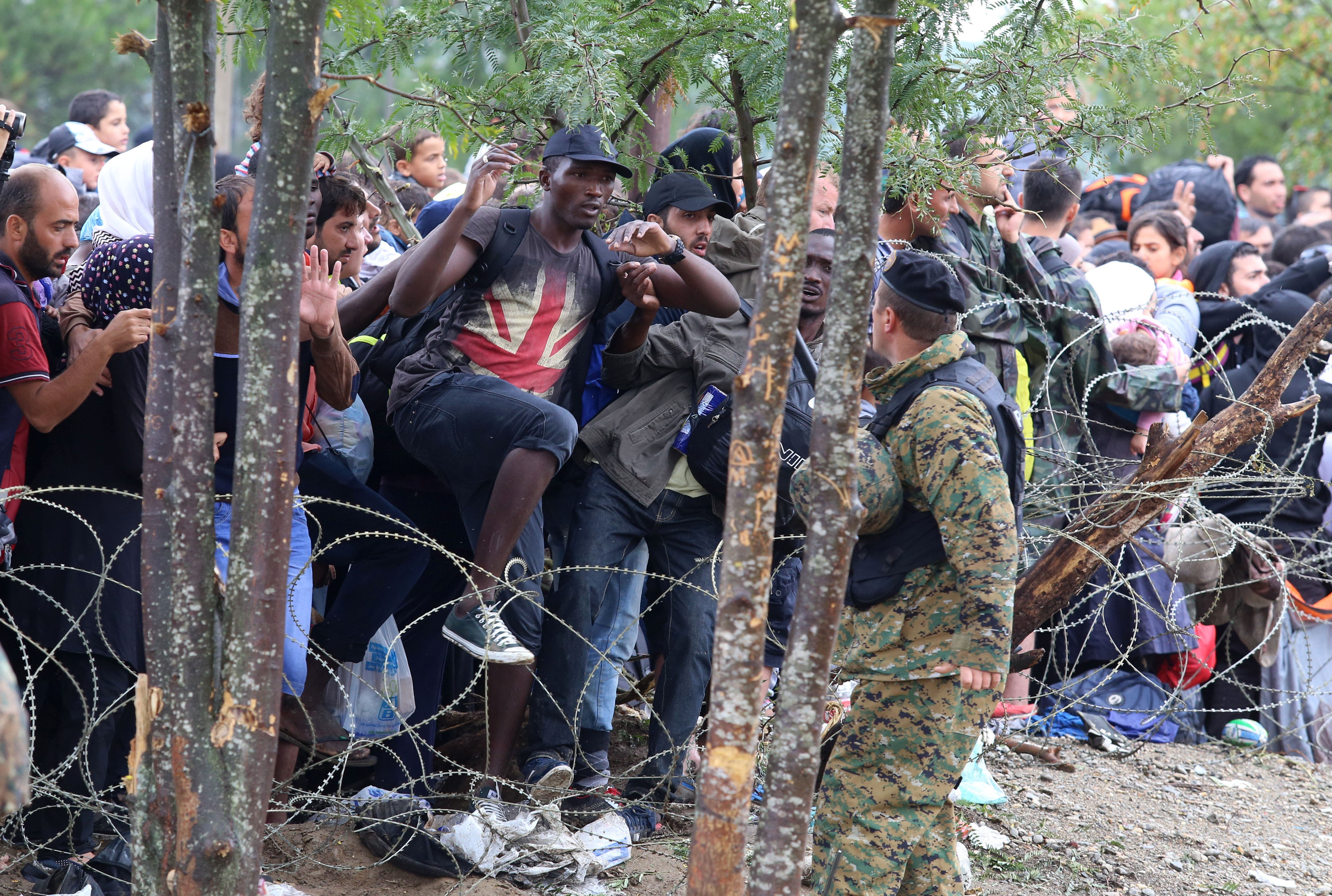 Migrants break the police blockade to enter into Macedonia from Greece, on the border line between the two countries, near the southern Macedonia's town of Gevgelija, on Saturday, Aug. 22, 2015.  (AP)