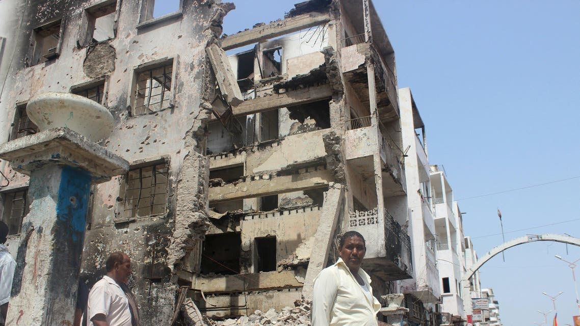 People walk past a building damaged by fighting recent between Houthi militants and fighters of the Southern Resistance, in Yemen's southern port city of Aden. (File photo: Reuters)
