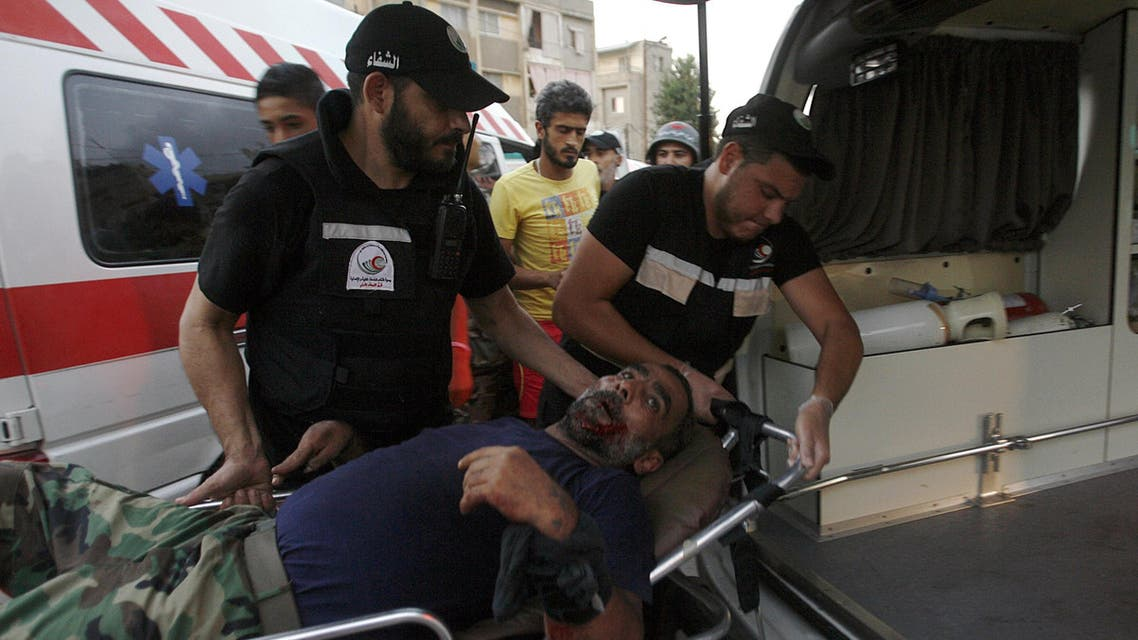 Members of the emergency services carry a wounded man on a stretcher following clashes in Ain El-Helweh Palestinian refugee camp near Lebanon's southern port city of Sidon on August 22. (AFP)