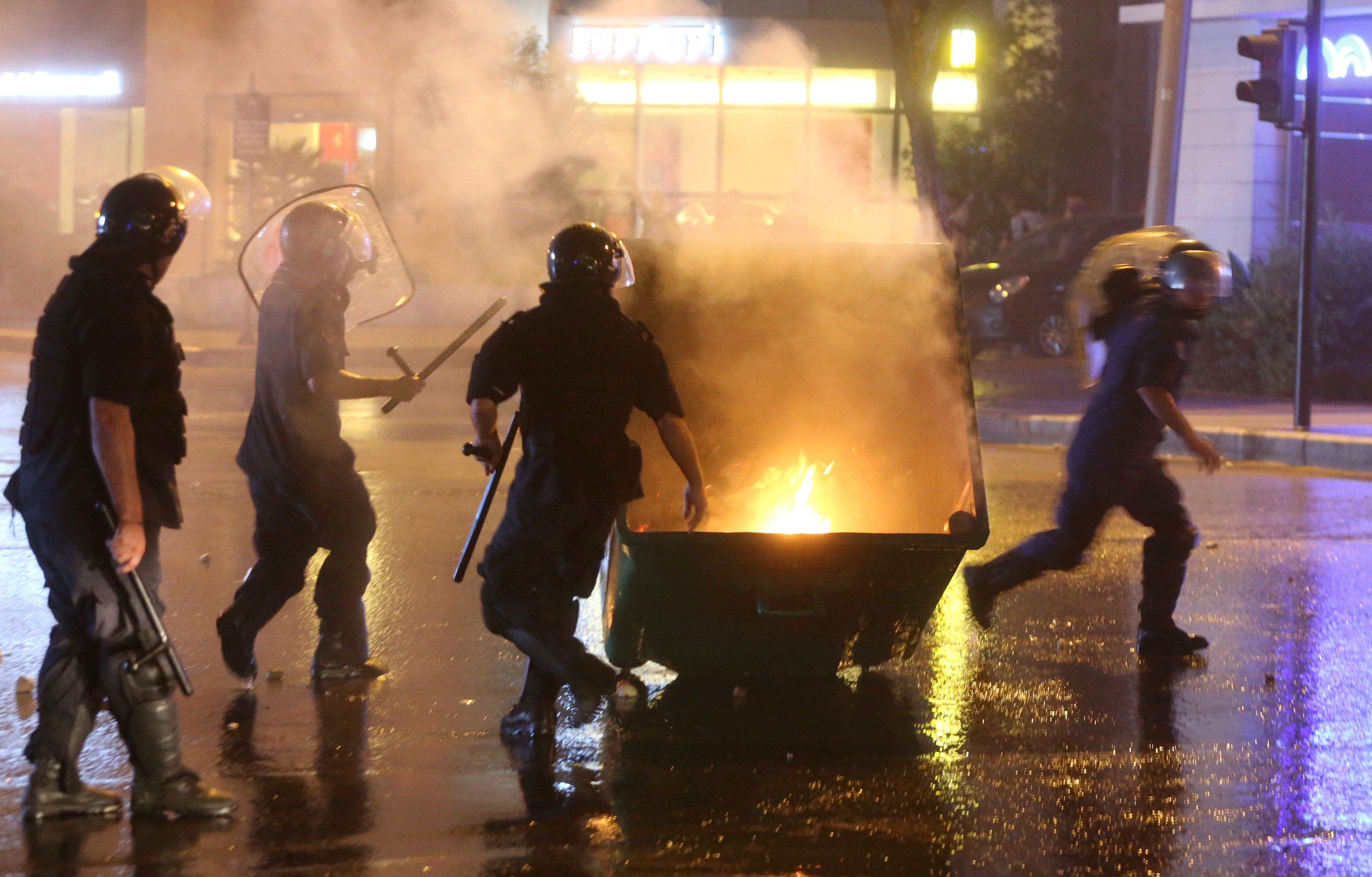 Lebanese security forces run towards a rubbish container set on fire by protesters (AFP)