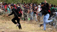 Thousands of migrants rush past police into Macedonia