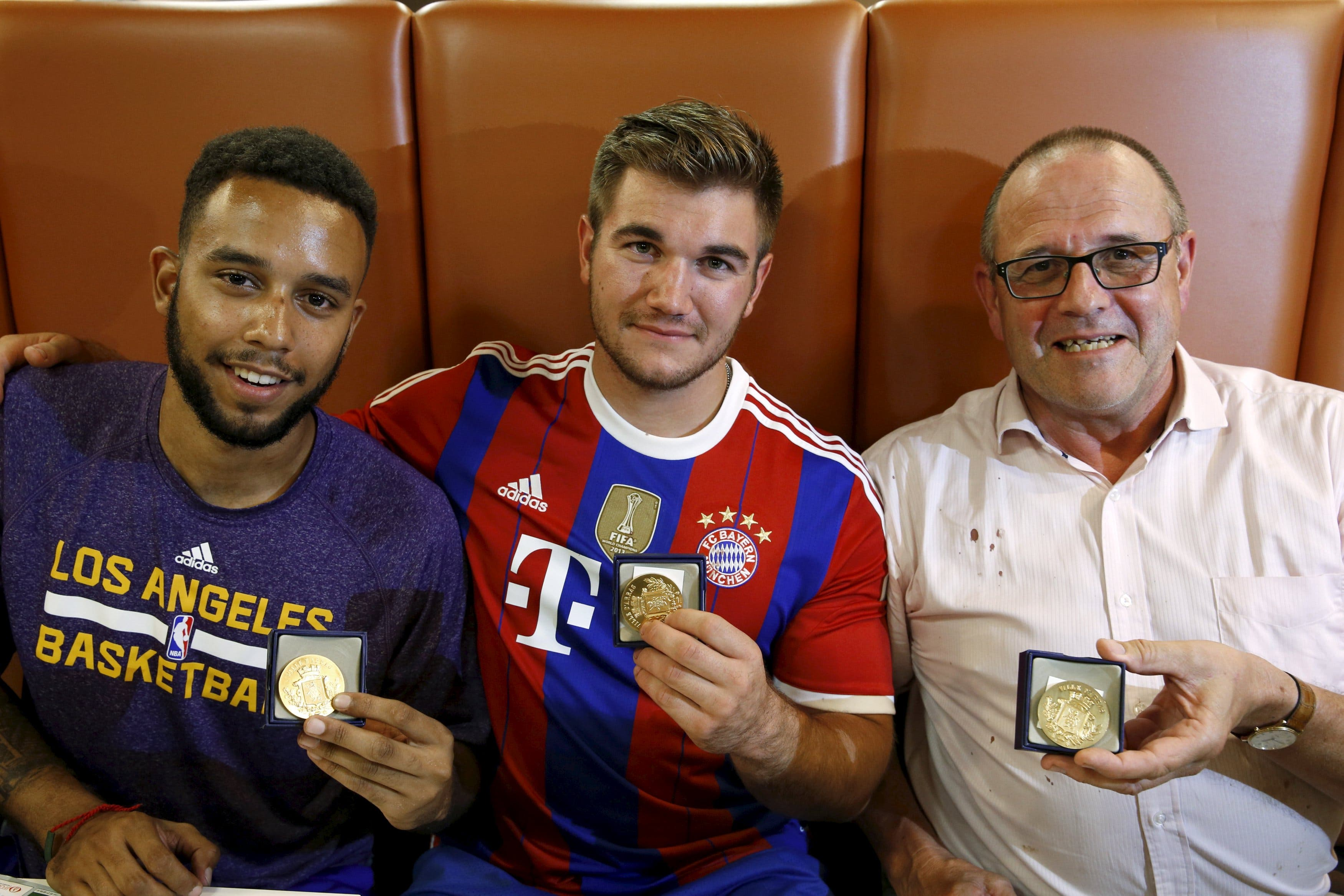 Sadler, Sharlatos, and Norman, three men who helped to disarm an attacker on a train from Amsterdam to France, pose with their medals at a restaurant in Arras, France. (File photo: Reuters)
