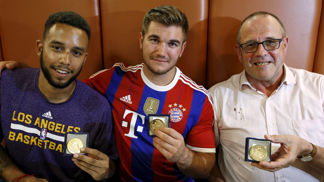 Sadler, Sharlatos, and Norman, three men who helped to disarm an attacker on a train from Amsterdam to France, pose with their medals at a restaurant in Arras, France. (Reuters)