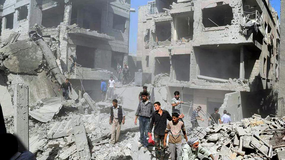 This picture released by the Douma Revolution News Network on their Facebook page, shows Syrians inspecting damage following a Syrian government airstrike on the Damascus suburb of Douma, Syria, Saturday, Aug. 22, 2015. Syrian activists said that at least 20 people have been killed and dozens wounded in government airstrikes on Douma. (Firas Abdullah/Douma Revolution News Network Facebook page via AP)