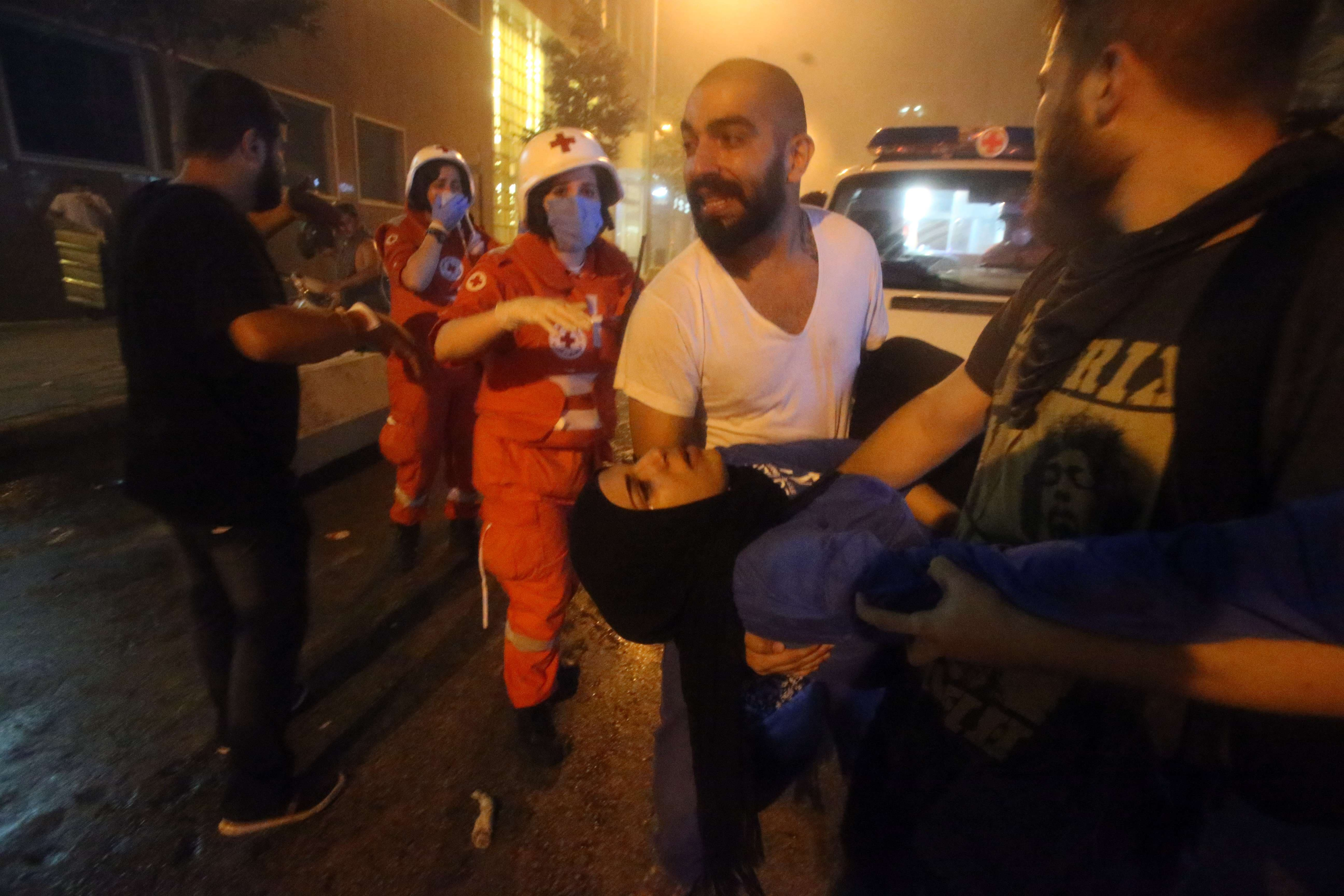 Lebanese protesters carry an injured girl during clashes with riot ...