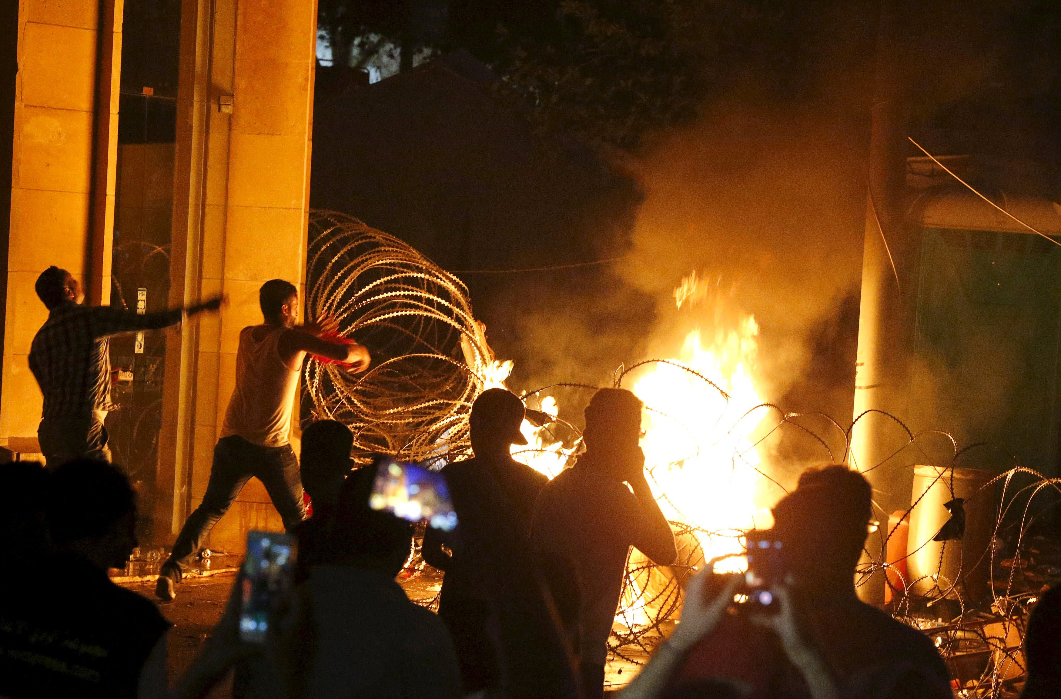 Protesters seen starting a fire (Reuters)